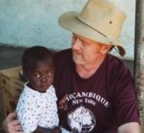 PhD Graduate Wayne Lavender with a small orphan on his lap